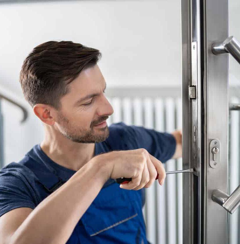 Mitarbeiter wechselt Türschloss aus